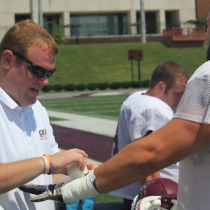 Andrew Brubaker athletic training student taping a wrist at football
